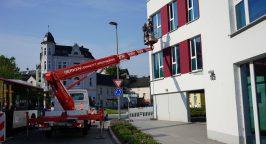 Ein Hubwagen befördert zwei Mitarbeiter der Weber Gruppe in Plettenberg an eine Fassade.