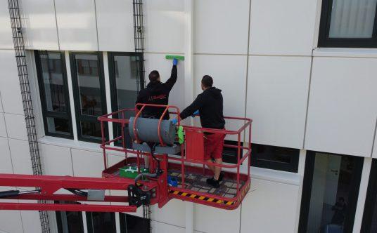Zwei Glas- und Gebäudereiniger der Weber Gruppe im Einsatz. Auf einer Hubbühne bearbeiten sie eine Fassade.