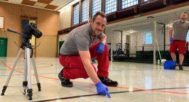 Ein Mitarbeiter der Weber Gruppe kniet vor einem Harzfleck in einer Sporthalle in der Stadt Hagen.
